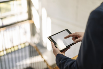 Businessman using tablet in staircase