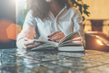 Close-up of paper book, notebook, diary on table in cafe. Businesswoman in white shirt sitting at table and reading book