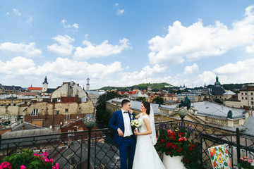 Bride puts her hands on groom's shoulder while they stand on the roof with great cityscape behind