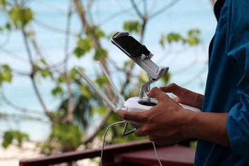 Men are using smartphones and remote control drone camera.
