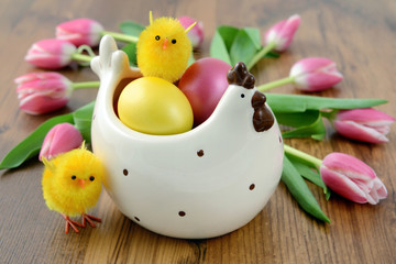 Easter eggs in chicken cup with bunch of pink tulips wooden background