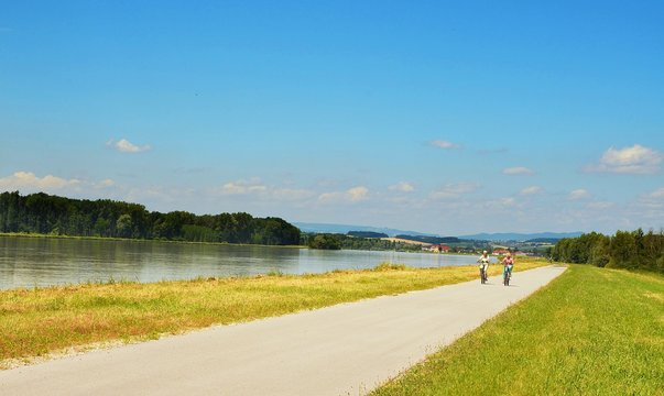 Well known Danube cycle trail running along the Danube river in Austria and two cyclists ride along cycle path during beautiful weather in the summer.