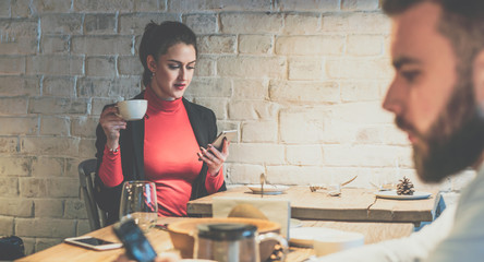 Young businesswoman sitting in cafe at wooden table, drinking coffee and using smartphone.