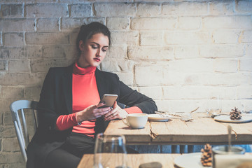 Young businesswoman sitting in cafe at wooden table and uses smartphone.On table cup of coffee.