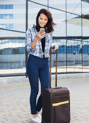 Young woman using smart phone with luggage suitcase. Vacations, travel and active lifestyle concept