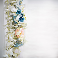 Fragment of a flower garland of wisteria and pions on a light background.