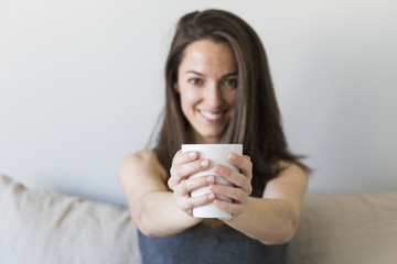 close up of woman hands holding a cup of coffee in her bedroom
