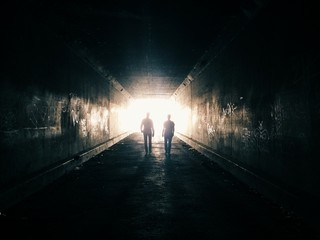 Two people walking through tunnel, illuminated
