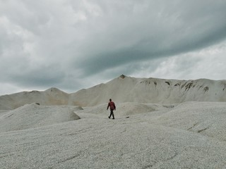 Man ascending sandy slope, distant