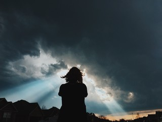 Silhouette of person looking at dramatic sky at sunset