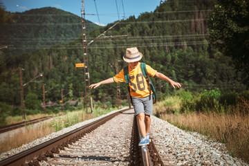 Little boy with backpack walks on railway