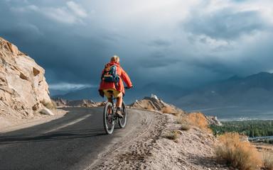 Bike tourist rides on Himalaya mountain road on way to buddist monastery
