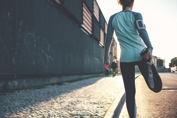 Athlete woman preparing for running on the city street. Legs warming and stretching. Sport tight clothes. Blurry background. Horizontal Wall mural