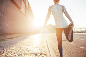 Athlete woman preparing for running on the city street. Legs warming and stretching. Sport tight clothes. Bright sun, blurry background. Horizontal Wall mural