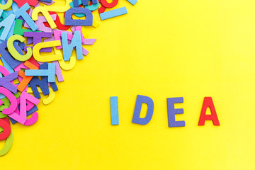 """Colorful wooden alphabet and word """"IDEA"""". Top view on yellow table"""