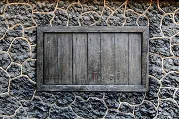 Wooden window in the wall of the black stone.
