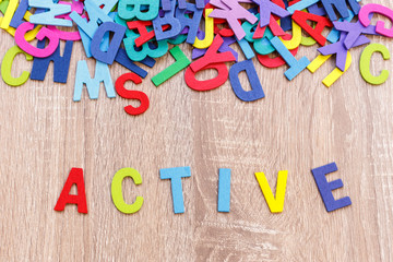 """Colorful wooden alphabet and word """"ACTIVE"""". Top view on grey wooden"""