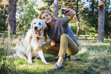 Young female doing selfie with labrador retriever dog in park
