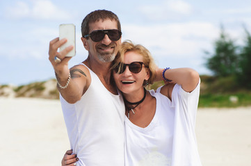 Portrait of mature smiling couple taking a selfie at the beach
