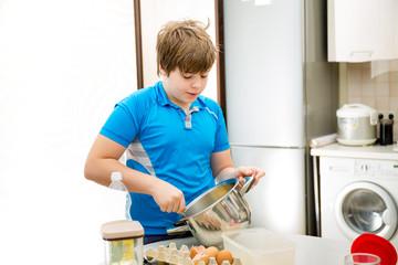 Boy kid baking muffins. Child schooler preparing muffins in the kitchen
