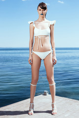 Sexy girl in a white swimwear wearing heels standing on pier over sea and sky horizon. Seductive model on the seaside in Summer