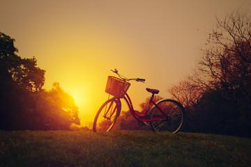 Landscape image of vintage bicycle on beautiful sunset