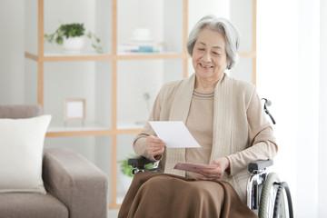 Senior Woman on Wheelchair Reading Letter