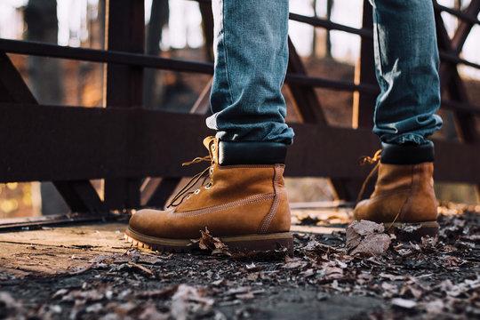 man wearing boots standing on bridge