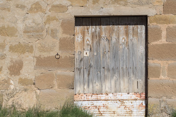 Rustic wooden door in hut of stone walls. Grass on the ground