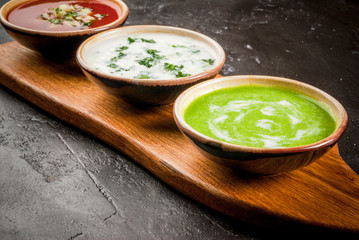 Selection of cold refreshing summer soups: tomato gazpacho, tarator, cream soup of green peas on a cutting board on a black concrete table close view copy space