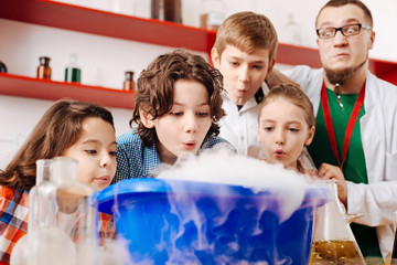 Enthusiastic positive children blowing on the chemical fume
