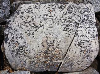 The ancient stone with the images of buddhas along trek on which a Buddhist mantras - Nepal, Himalayas