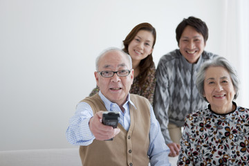 Senior Couple and Adult Daughter and Son Watching Tv, Senior Man Pointing Remote Control To Camera