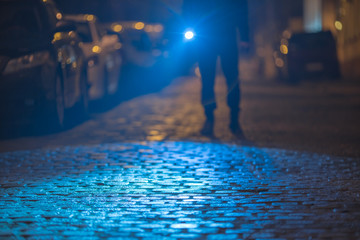 The man with a flashlight inspect the street. Evening night time Fotomurales