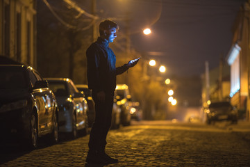 The man phone on the street. Evening night time. Telephoto lens shot