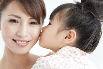 Girl kissing mother, woman looking at camera, close up, white background