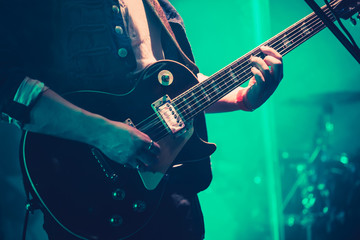 Electric guitar player on stage in green light