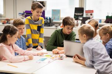 happy children with laptop at robotics school