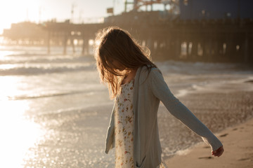 Girl in dress and cardigan walks the beach by the Santa Monica Pier