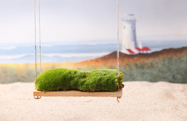 A newborn background backdrop with moss on a swing over a sandy beach with a lighthouse and ocean waves in the background.