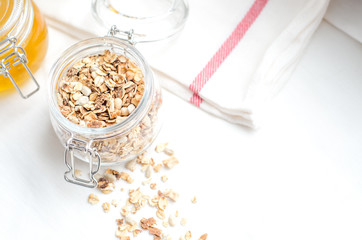 Top view breakfast of homemade granola cereal with nuts and fruit, honey with drizzlier on white background. Healthy food, Diet, Detox, Clean Eating, Vegetarian concept.