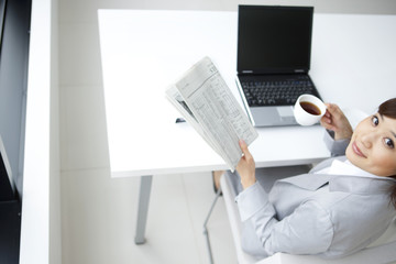 Portrait of young businesswoman holding newspaper and coffee cup
