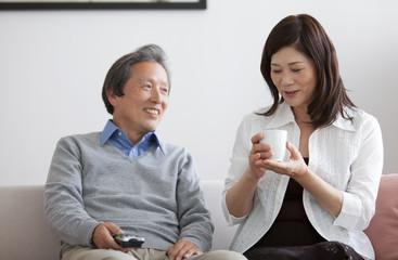 Couple sitting on sofa talking