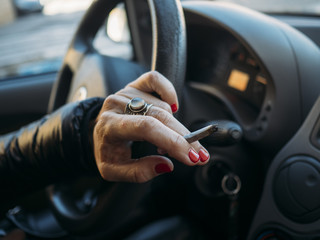 Cigarette in the hand with steering wheel of car