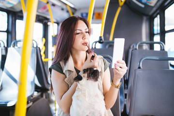 Beautiful young woman sitting in city bus, putting on lipstick and holding her pug dog in lap.