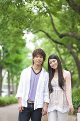 Portrait of young couple standing side by side smiling