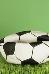 A flat football on grass