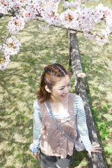 Young woman standing near cherry blossom tree