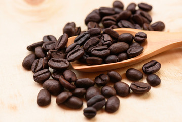 Coffee beans and wooden scoop on wooden background.