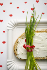 A bunch of fresh chives on a bread with cream cheese